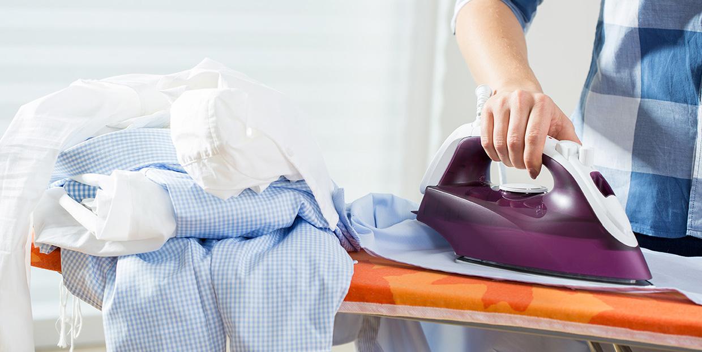 détail photo d'une personne faisant du repassage, fer à repasser, table à repasser, pile de chemises prêtes à repasser, aide aux travaux ménagers, services de proximité, Bel'Age SP, Grenoble