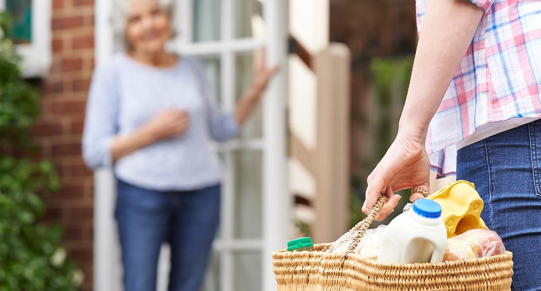 détail d'une photo d'une personne de dos avec un panier de courses qui livre une personne âgée à domicile, services de proximité, Bel'Age SP, Grenoble, aide aux courses
