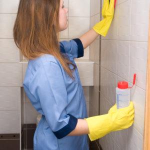 photo d'une femme en blouse bleue nettoyant les murs carrelés d'une salle de bain. Femme avec des gants ménagers jaune et un flacon de produit dans la main droite, Bel'Age Services de Proximité, Grenoble, Services à domicile, travaux ménagers, aide ménagère