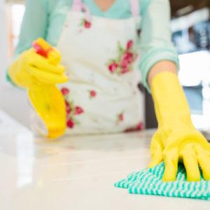 Photo détail d'une femme nettoyant une surface de plan de travail, avec des gants ménagers jaune, un chiffon à carreaux vert ainsi qu'un vaporisateur jaune et blanc, Bel'Age Services de Proximité, Grenoble, services à domicile, aide ménagère, travaux ménagers