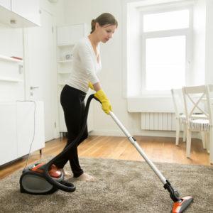 photo d'une femme habillée en noir et blanc passant l'aspirateur sur un tapis gris, Bel'Age Services de Proximité, Grenoble, services à domicile, travaux ménagers, aide ménagère